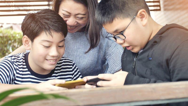 Het Aziatische van de familiemoeder en zoon letten op op mobiele telefoon royalty-vrije stock fotografie