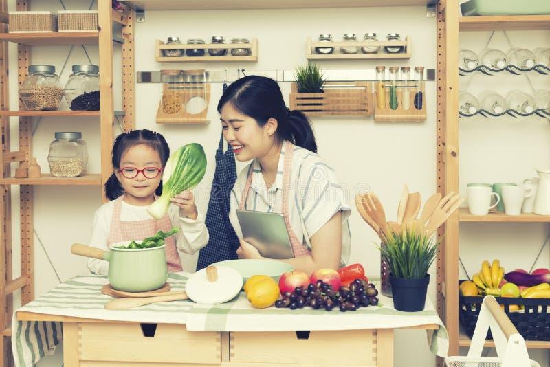 Het Aziatische van de vrouwenmamma en dochter spel samen in keuken, de tablet van de mammagreep voor onderwijst meisje hoe te kok royalty-vrije stock foto