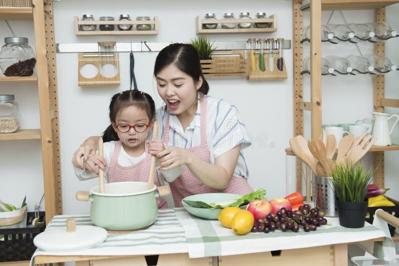 Het Aziatische van de vrouwenmamma en dochter spel samen in keuken, de tablet van de mammagreep voor onderwijst meisje hoe te kok royalty-vrije stock afbeelding