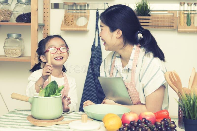Het Aziatische van de vrouwenmamma en dochter spel samen in keuken, de tablet van de mammagreep voor onderwijst meisje hoe te kok royalty-vrije stock foto's