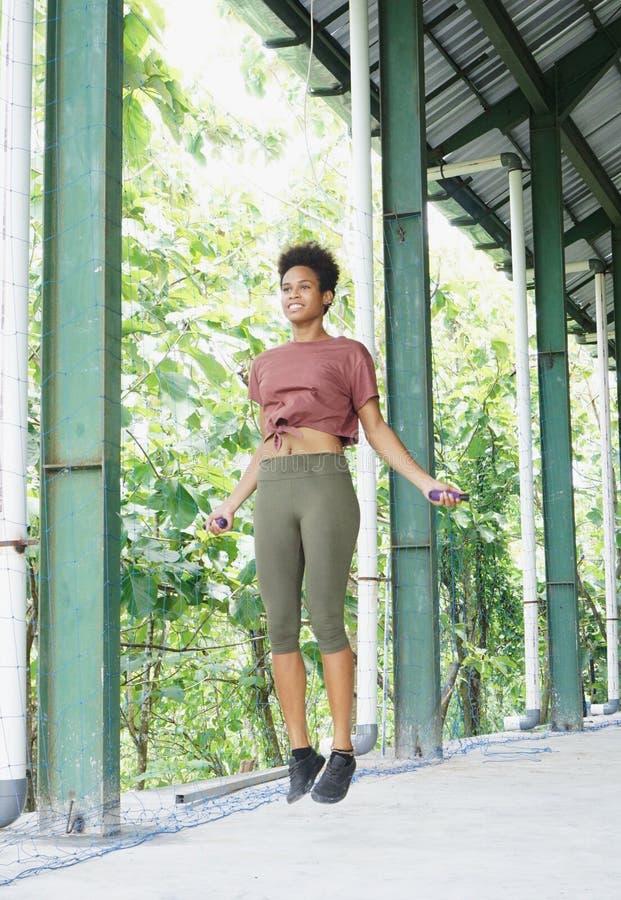 het Aziatische vreedzame meisje die van de eilandbewoneratleet met afro uitoefenend routines het overslaan presteren stock foto
