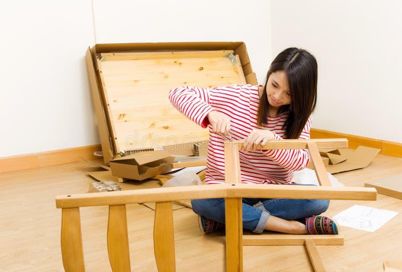 Het Aziatische vrouw gebruiken strooit bestuurder voor het assembleren van meubilair uit stock afbeeldingen