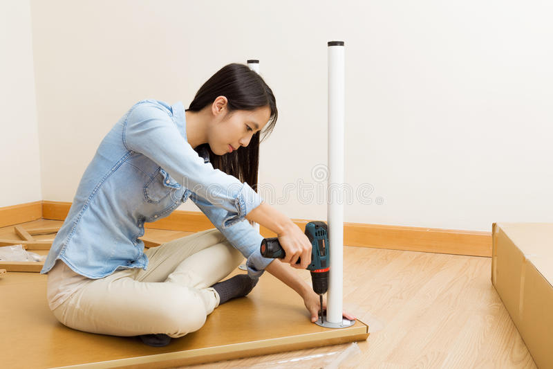 Het Aziatische vrouw gebruiken strooit bestuurder voor het assembleren van meubilair uit stock foto
