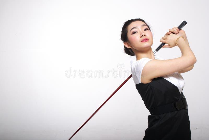 Het Aziatische vrouw golfing stock foto