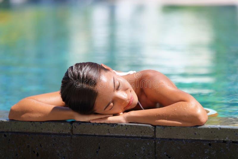 Het Aziatische vrouw ontspannen die - pool spa terugtocht zonnebaden royalty-vrije stock afbeeldingen