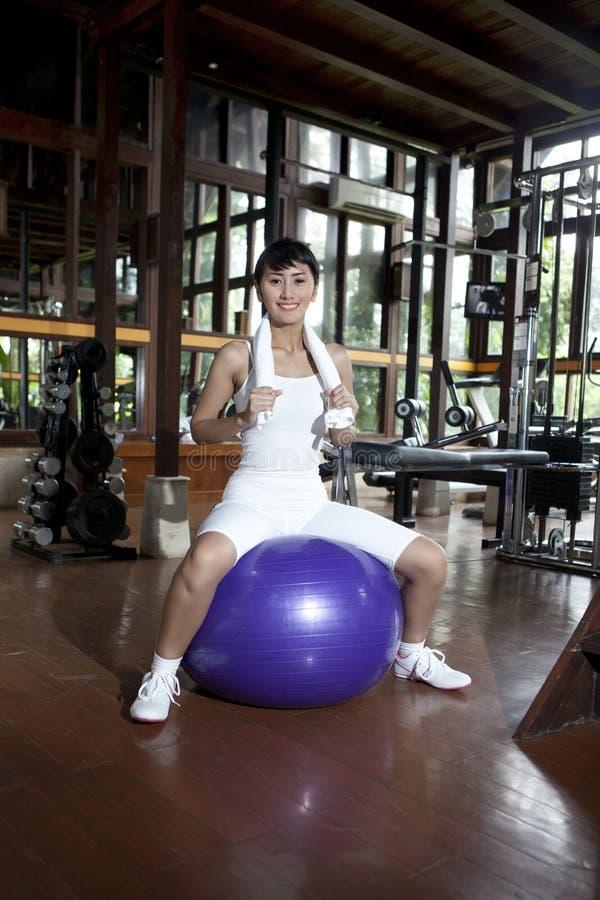 Het Aziatische vrouw stellen met Zwitserse bal in een gymnastiek stock afbeelding