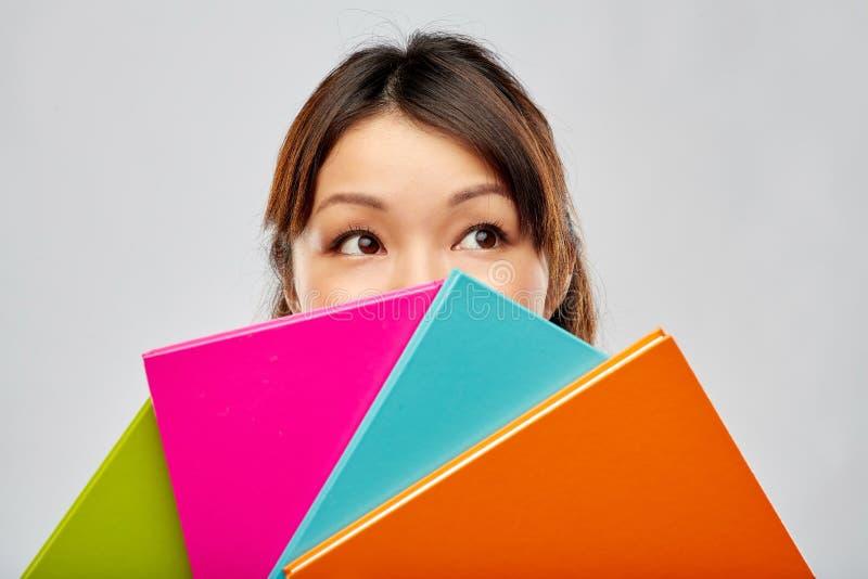 Het Aziatische vrouw of studenten verbergen achter notitieboekjes stock foto's