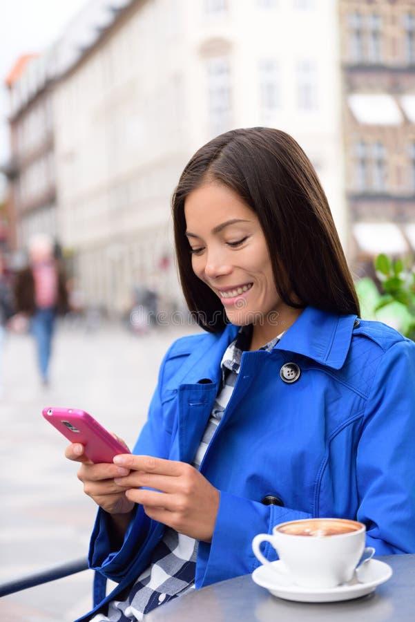 Het Aziatische vrouw texting op telefoon bij openluchtkoffie stock afbeelding