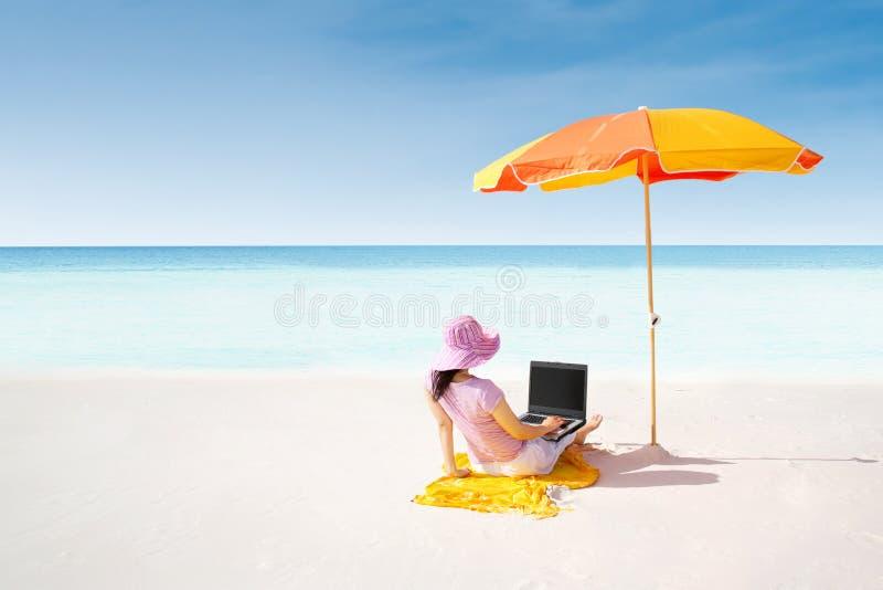 Het Aziatische vrouw typen op laptop onder parasol bij strand stock afbeelding
