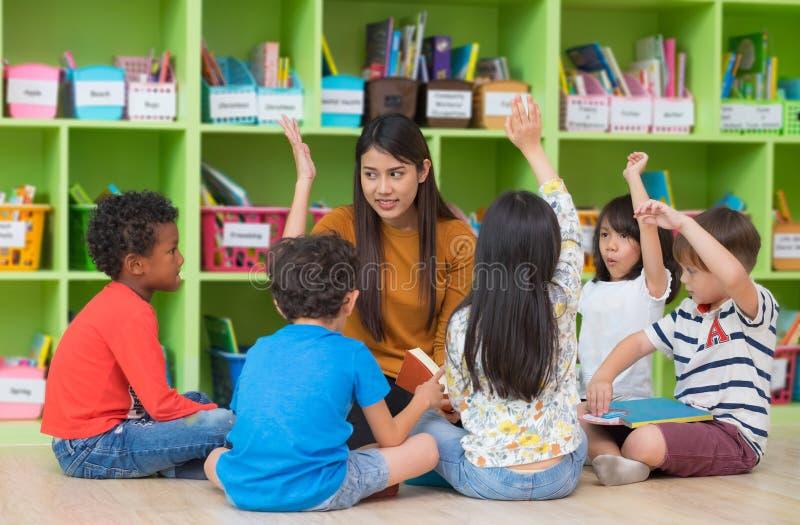 Het Aziatische vrouwelijke leraarsonderwijs en omhoog het vragen van de gemengde hand van rasjonge geitjes stock afbeelding