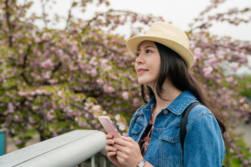 Het Aziatische vrouwelijke mobiel gebruiken en het kijken plezierig stock fotografie