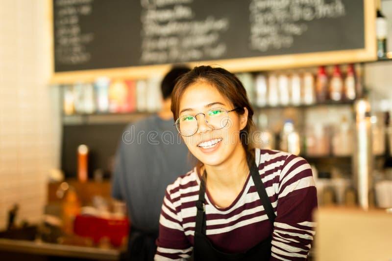 Het Aziatische vrouwen amiling werk in kleine bedrijfseigenaarvoedsel en drinkt koffie royalty-vrije stock fotografie