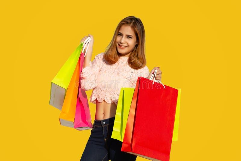 Het Aziatische vrouwen Mooie meisje houdt het winkelen zakken en het glimlachen op gele achtergrond stock afbeelding