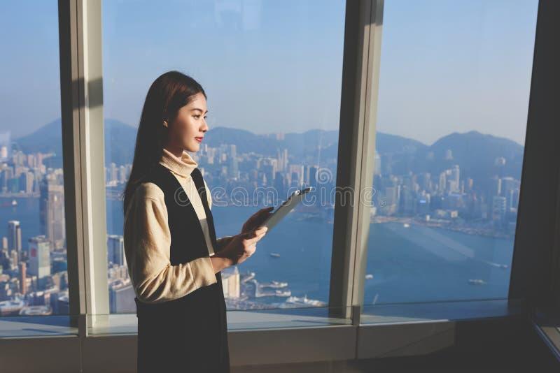 Het Aziatische wijfje gebruikt aanrakingsstootkussen, terwijl zich in luxebinnenland tegen venster bevindt royalty-vrije stock foto