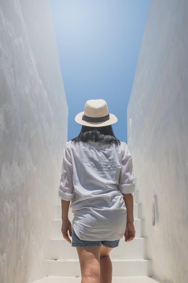 Het Aziatische witte overhemd van de vrouwenslijtage en weefselhoed die op concrete treden naar boven gaan stock fotografie