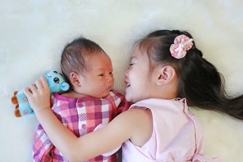 Het Aziatische zuster spelen met het pasgeboren baby liggen op witte bontachtergrond stock afbeelding