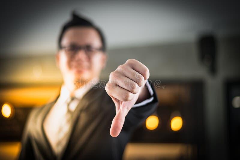 Het Aziatische zwarte kostuum die van de zakenmanslijtage en duim zich terugtrekken tonen royalty-vrije stock afbeelding
