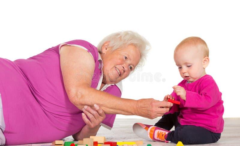 Het baby-sitting van Gran haar klein kleinkind stock foto's