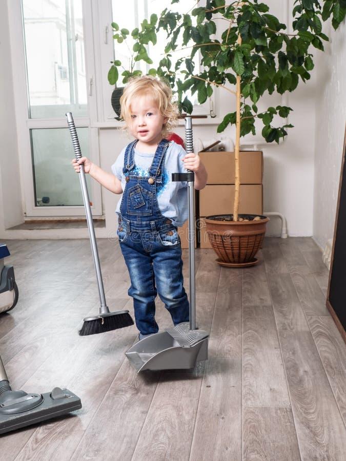 Het babymeisje in blauwe denimoverall maakt het huis schoon en veegt de vloer met een bezem stock afbeeldingen