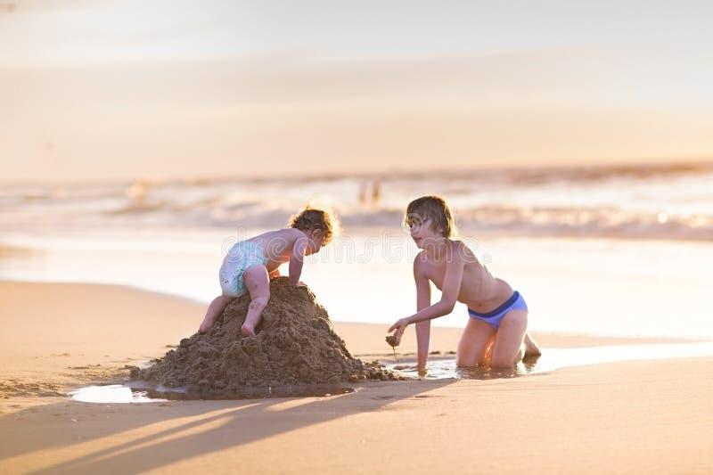 Het babymeisje die zandkasteel beklimmen haar broer was builded stock afbeeldingen