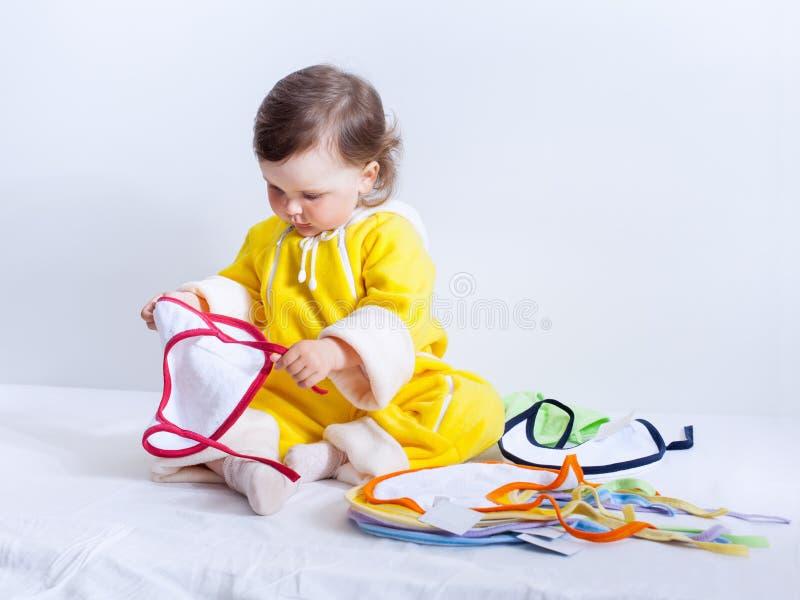 Het babymeisje in gele kruippakjes kiest slab stock foto's