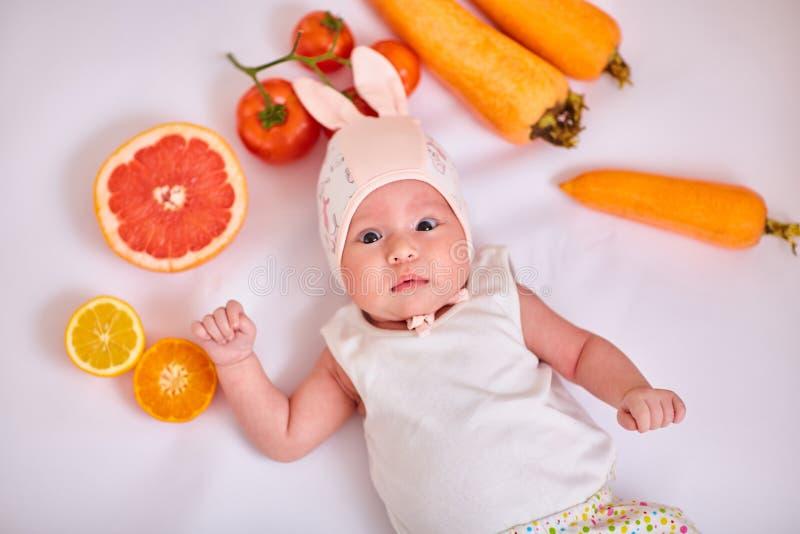 Het babymeisje in hoed met konijntjesoren ligt op witte achtergrond met vruchten en groenten - gezond voedsel, wortelen, tomaten, stock afbeeldingen