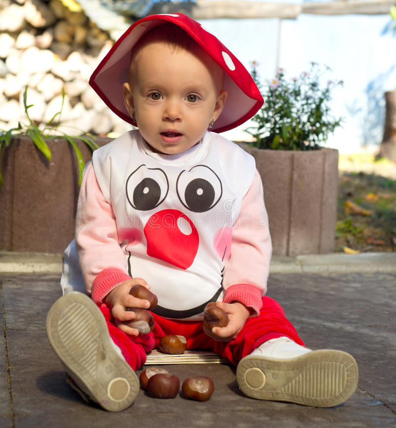 Het babymeisje kleedde zich als een paddestoel stock foto