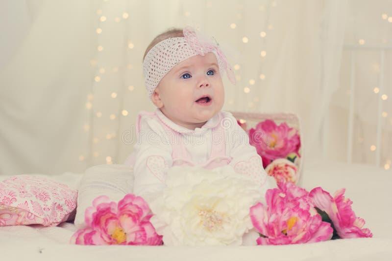 Het babymeisje ligt op bed met roze bloemen royalty-vrije stock afbeeldingen