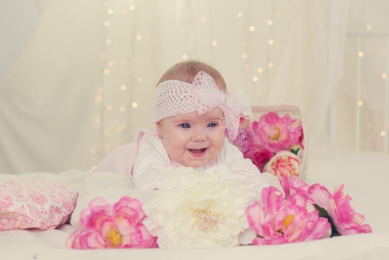 Het babymeisje ligt op bed met roze bloemen stock fotografie