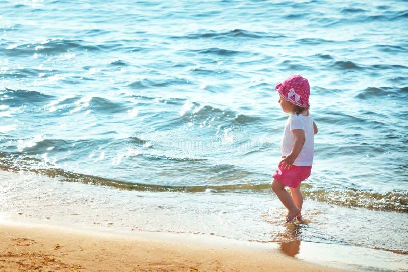 Het babymeisje loopt op het strand royalty-vrije stock afbeelding
