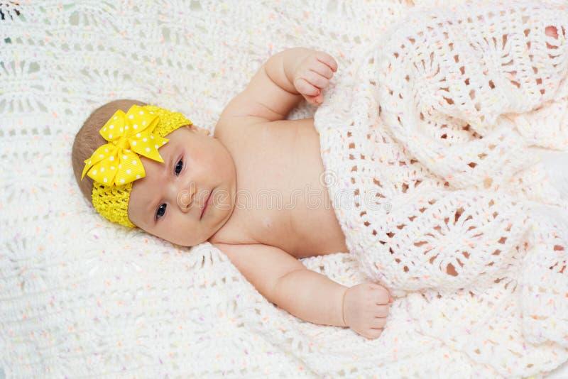 Het babymeisje van twee maand met geel lint royalty-vrije stock fotografie