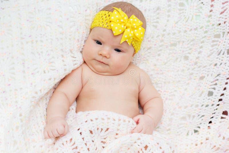 Het babymeisje van twee maand met geel lint op hoofd royalty-vrije stock afbeeldingen