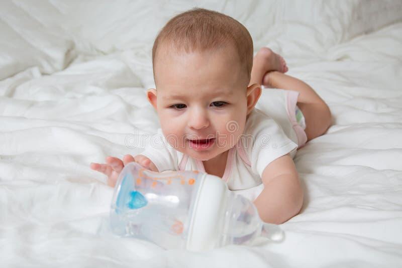 Het babymeisje wil handen drinken en trekken aan plastic fles water Witte achtergrond stock afbeeldingen