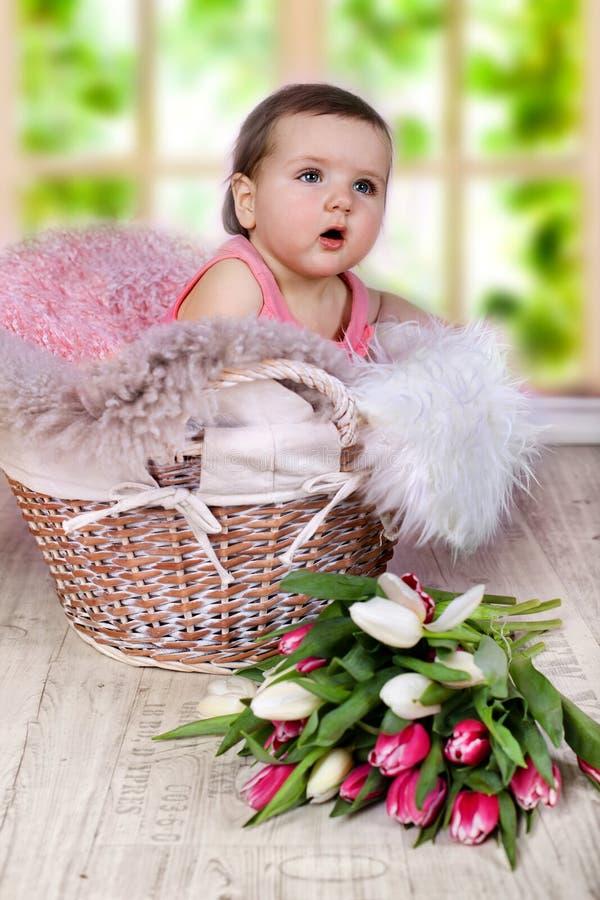 Het babymeisje zit in een pluizige mand stock foto's