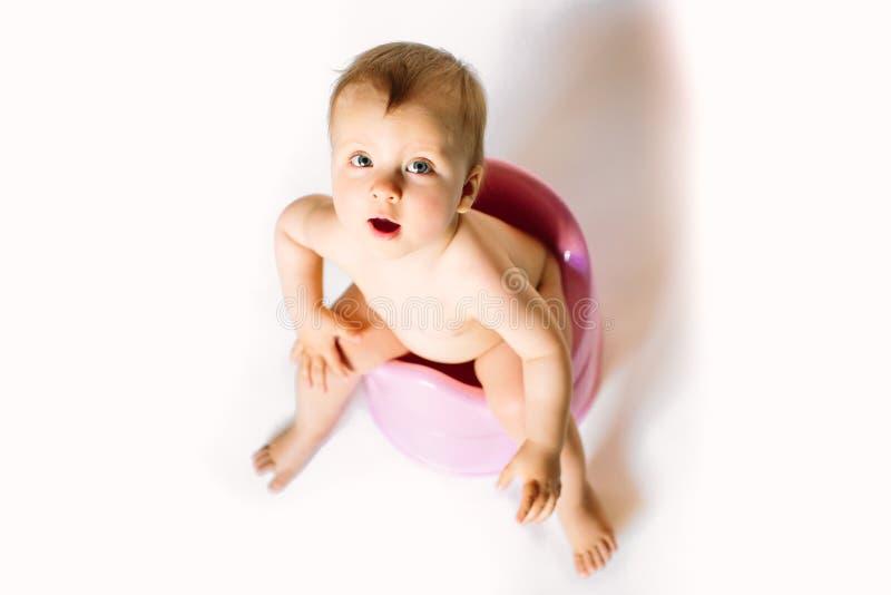 Het babymeisje zit op een pot van kinderen, toilet op een witte achtergrond stock afbeelding