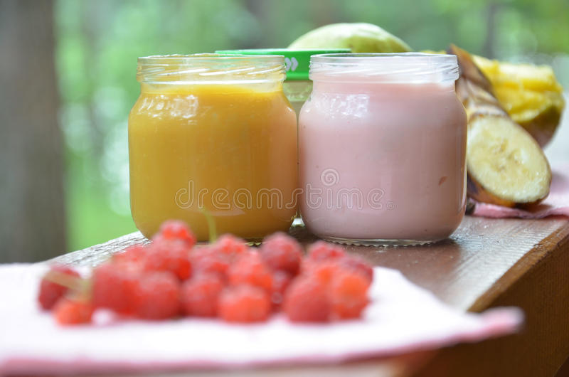 Het babyvoedsel in kruiken maakt fijngestampt voedsel op een achtergrond van gebladerte, met een perenbanaan, fopspeen en een lep royalty-vrije stock foto's