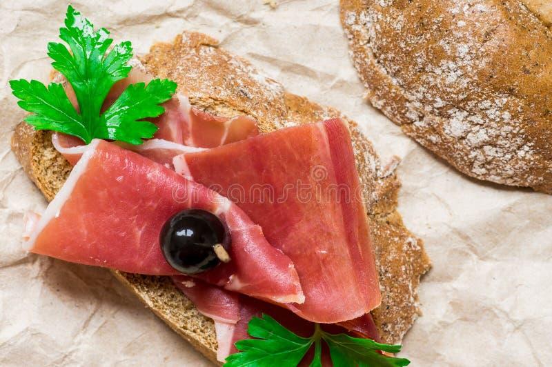 Het bacon van het straatvoedsel, toost, verse kruiden en olijven stock afbeelding