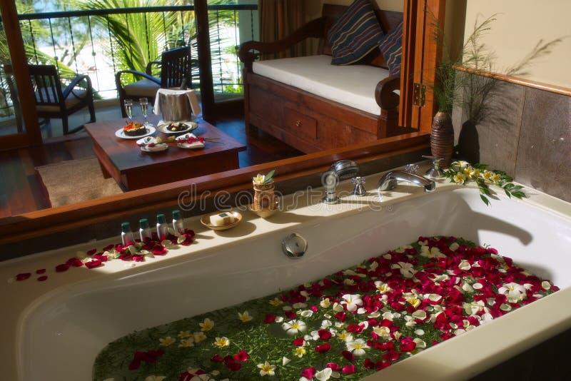 Het bad van het KUUROORD met bloembloemblaadjes stock foto's