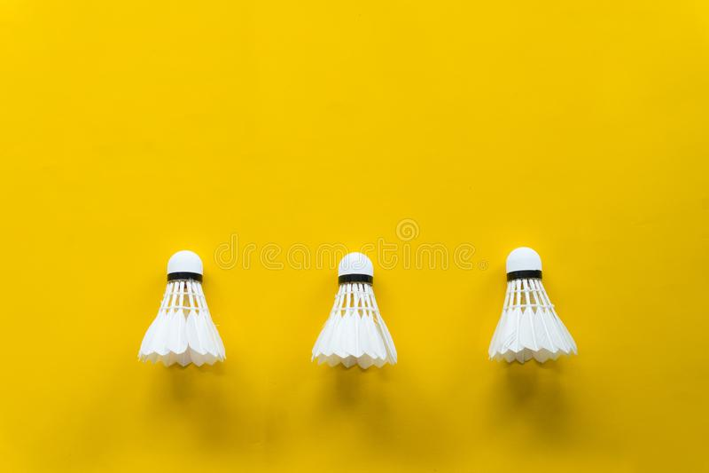 Het badminton van de pendelhaan met gele achtergrond royalty-vrije stock afbeeldingen