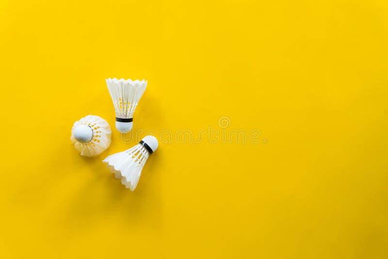 Het badminton van de pendelhaan met gele achtergrond stock afbeeldingen
