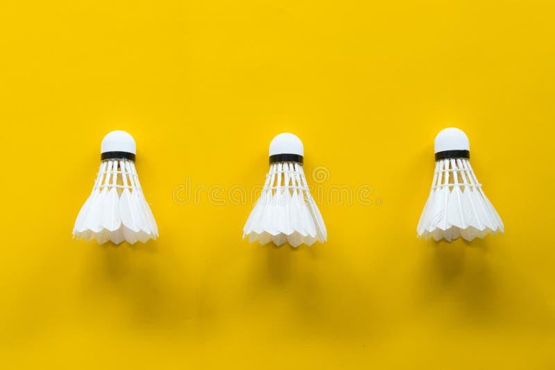 Het badminton van de pendelhaan met gele achtergrond royalty-vrije stock afbeelding