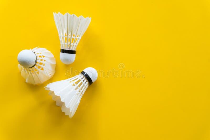 Het badminton van de pendelhaan met gele achtergrond royalty-vrije stock foto's