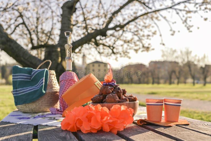 Het bakken en divers voedsel, dranken en wijn voor lunch op de aard Oranjevayahoed en toebehoren Traditionele donuts voor Koning stock afbeeldingen