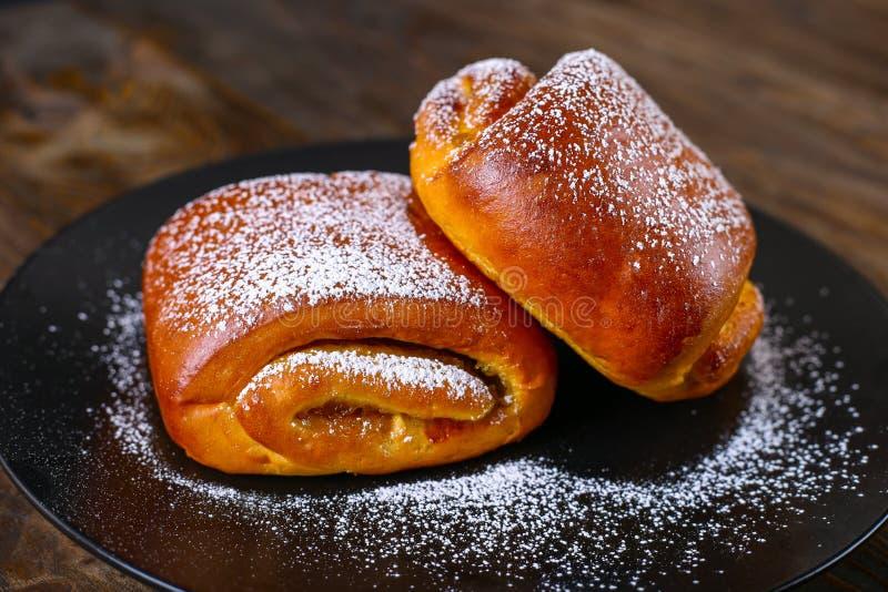 Het bakken op een zwarte plaat Zoete Broodjes met Suikerglazuursuiker stock foto
