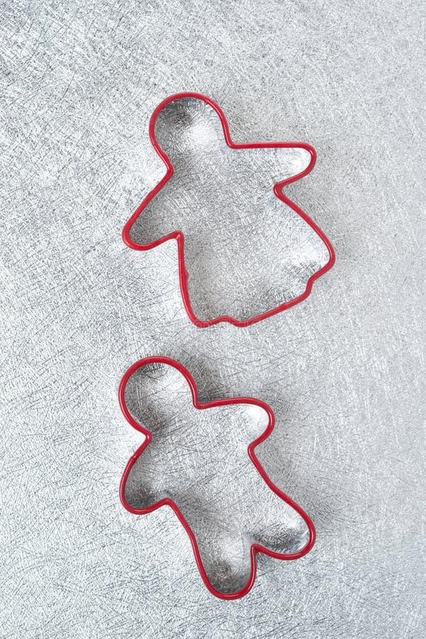 Het bakken twee schotel in de vorm van kleine mensen op een zilveren achtergrond stock fotografie