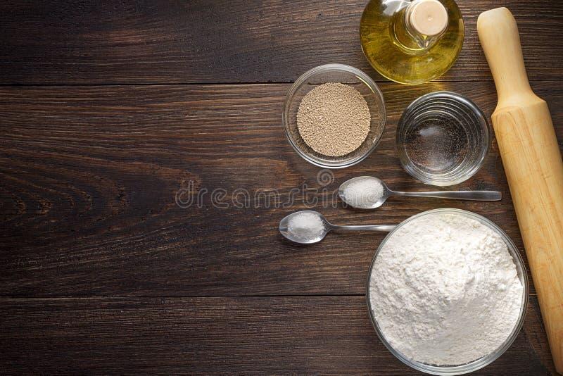 Het bakken van houten achtergrond met ingrediënten voor pizzadeeg stock foto