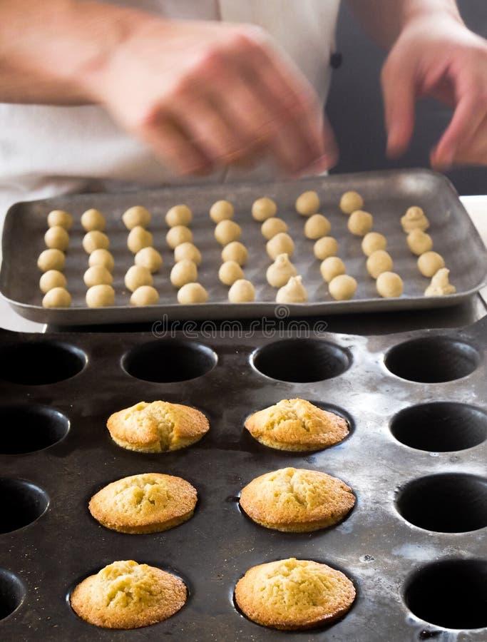 Het bakken van kleine cakes in een bakseldienblad royalty-vrije stock afbeeldingen