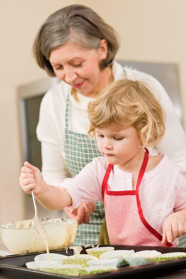 Het baksel van de vrouw en van het meisje cupcakes samen stock fotografie