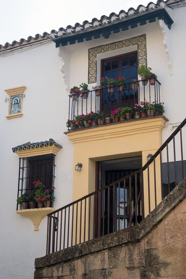 Het balkon van het metaalsmeedijzer met bloemen, vensters en een pictogram op de witte muur Traditioneel Spaans huis in de stad v stock afbeelding