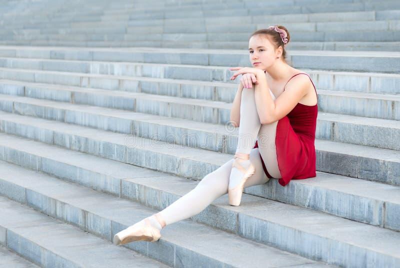 Het ballerinameisje zit op de stappen in een balletkleding royalty-vrije stock foto's